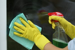 Female househlod,glass cleaning with rag and spray